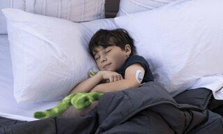 """Lovoje miegantis vaikas su """"Dexcom ONE"""" jutikliu ant rankos"""