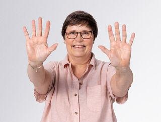 Moteris, pakėlusi rankas prie fotoaparato, rodo pirštus be dūrių