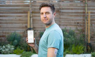 Vīrietis rāda savu tālruni ar Dexcom lietotni un Dexcom ONE sensoru uz rokas