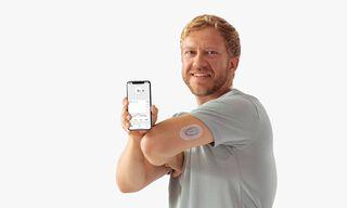"""Vyras rodo """"Dexcom"""" programėlę telefone ir """"Dexcom"""" jutiklį ant rankos"""
